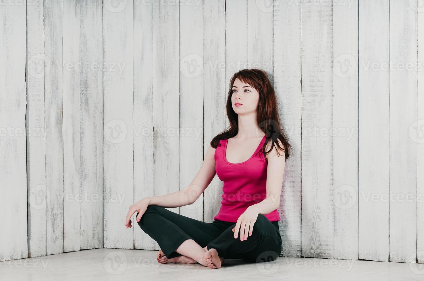 ragazza in top rosa, seduta a gambe incrociate sul pavimento, sfondo chiaro foto