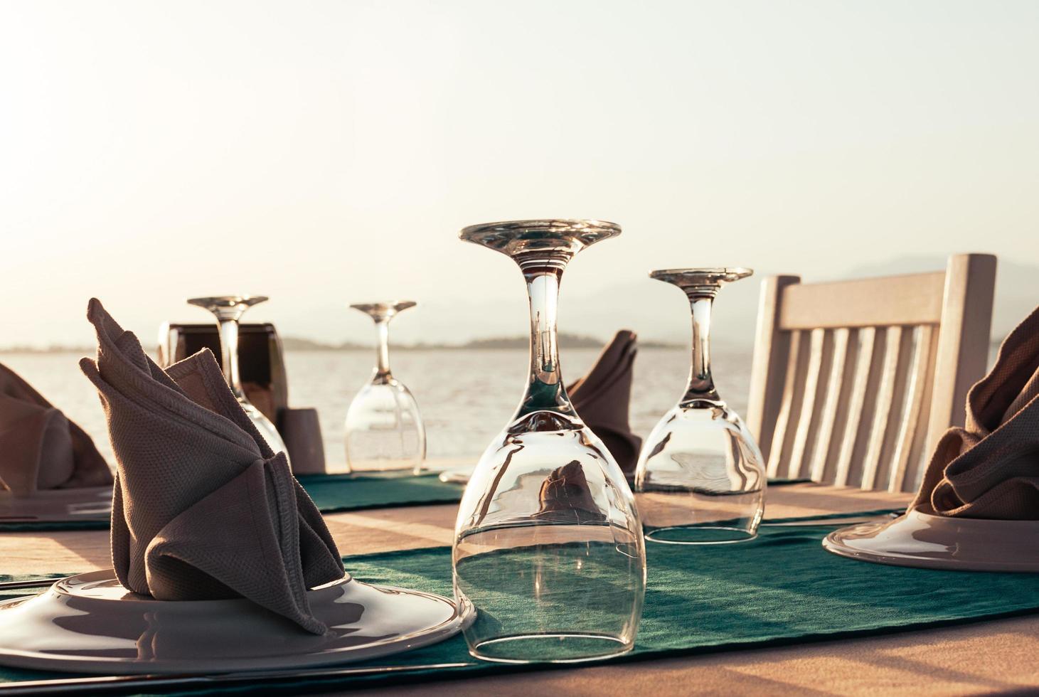 apparecchiare la tavola al ristorante sulla spiaggia al tramonto foto
