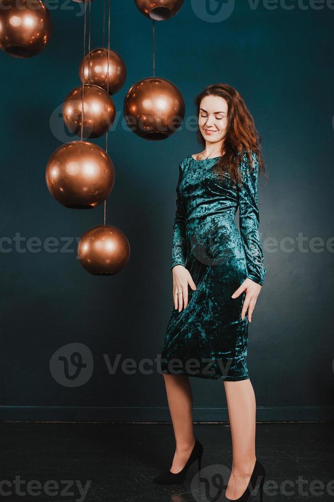 bella donna in abito blu verde, sorridente, concetto di lusso foto