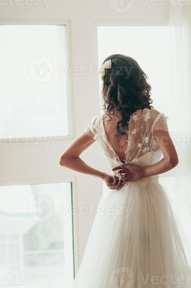 sposa che si abbottona il vestito vicino alla finestra, vista dalla sua schiena foto