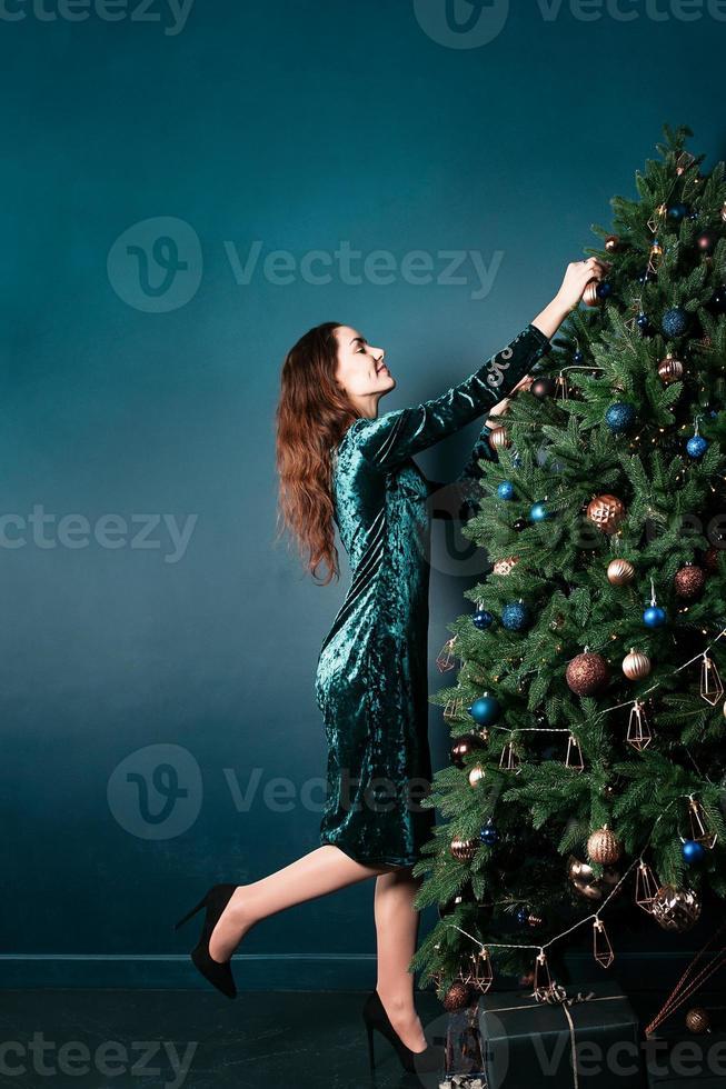 affascinante giovane donna sorridente che decora l'albero di natale foto
