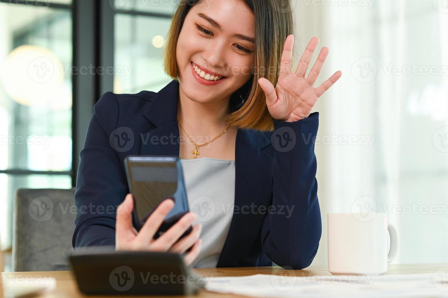 la donna d'affari in giacca e cravatta che si fa un selfie con uno smartphone. foto