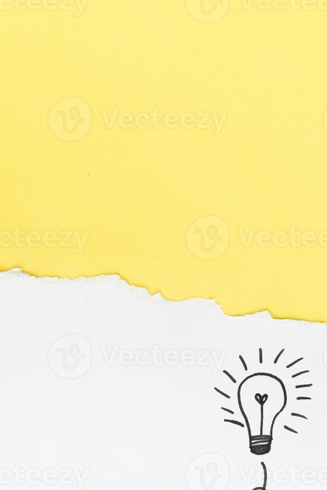 carta gialla con lampadina disegnata a mano su sfondo bianco foto