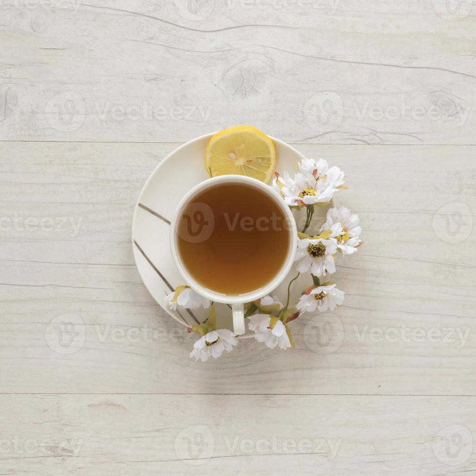 tazza da tè al limone con fiori e limone foto
