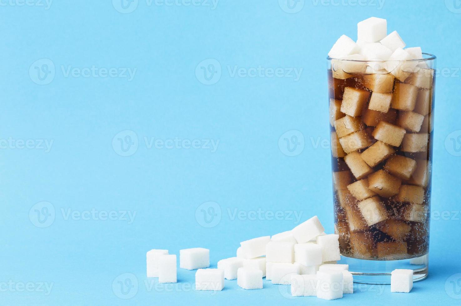 bicchiere di bibita con zollette di zucchero foto