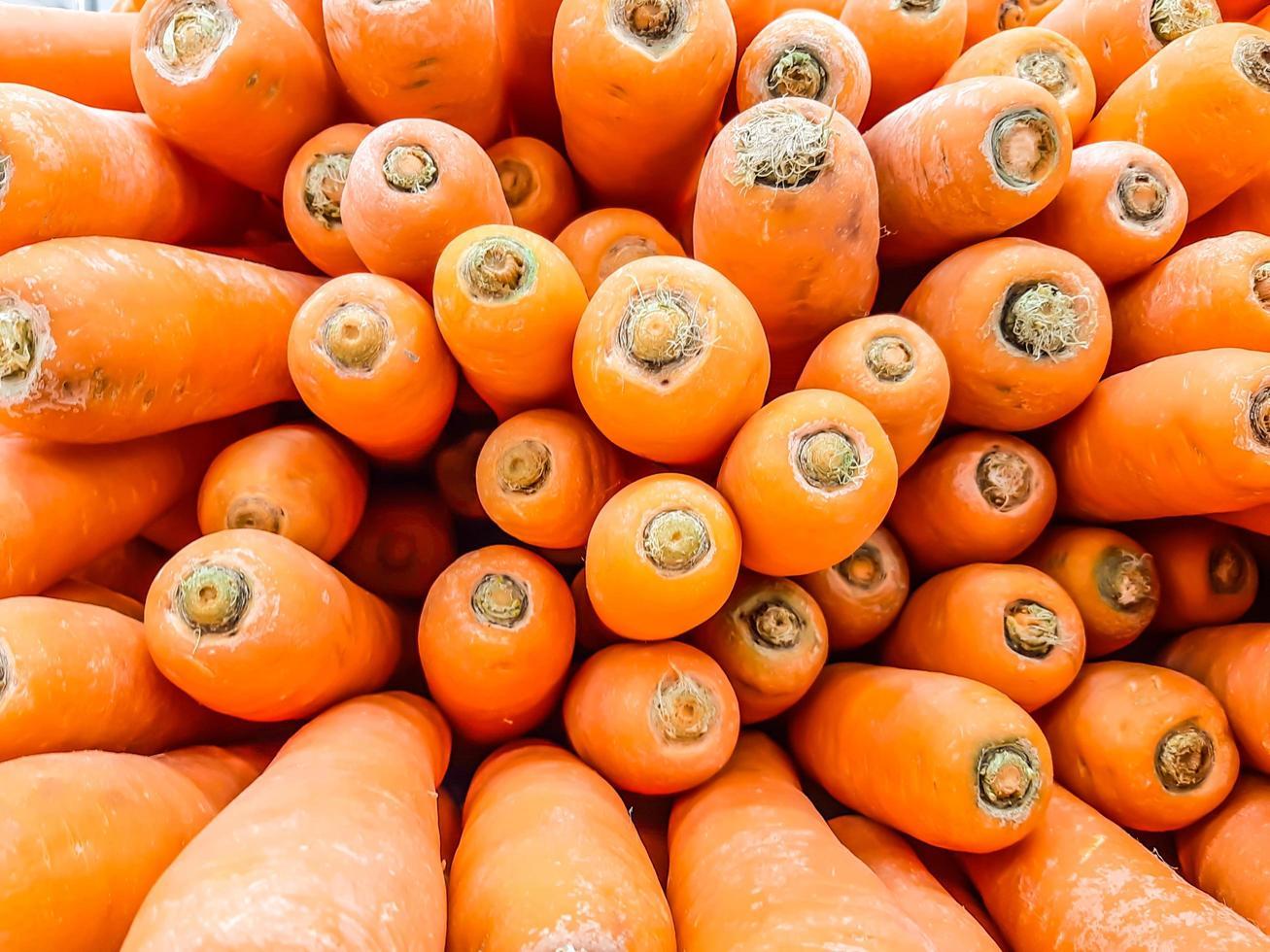 carota biologica. trama di sfondo di grandi carote arancioni fresche, le carote sono buone per la salute, carote mature sane per preparare il pasto foto