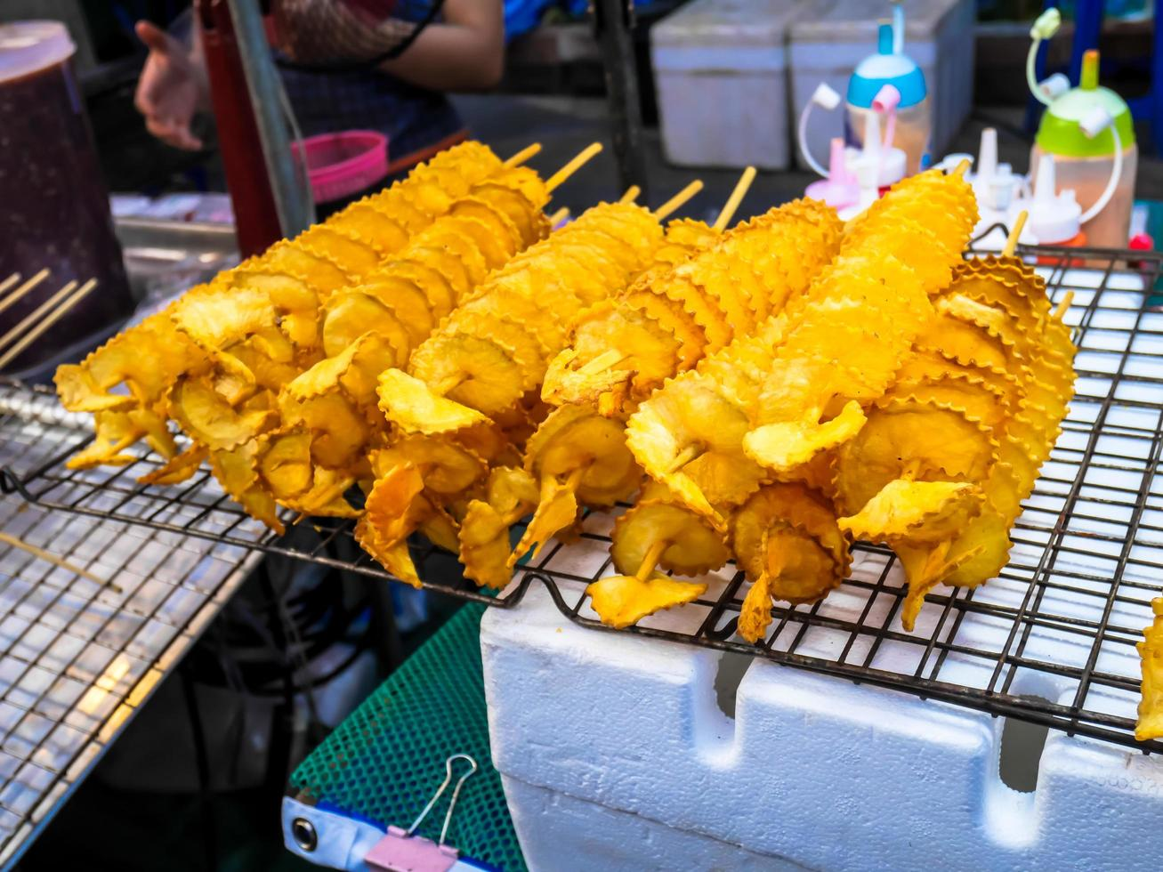 patate fritte a spirale, su bastoncini di legno, a spirale. vendere cibo al mercato. foto