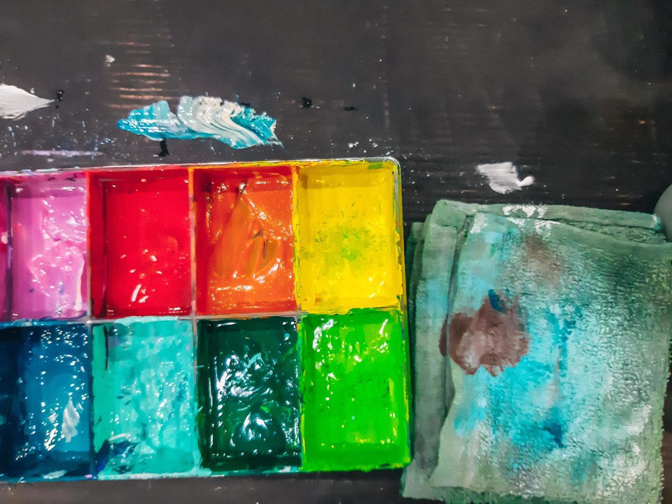 acquerello in una tavolozza, la tavolozza colori ad acqua sul tavolo, molti colori nella tavolozza colori ad acqua foto