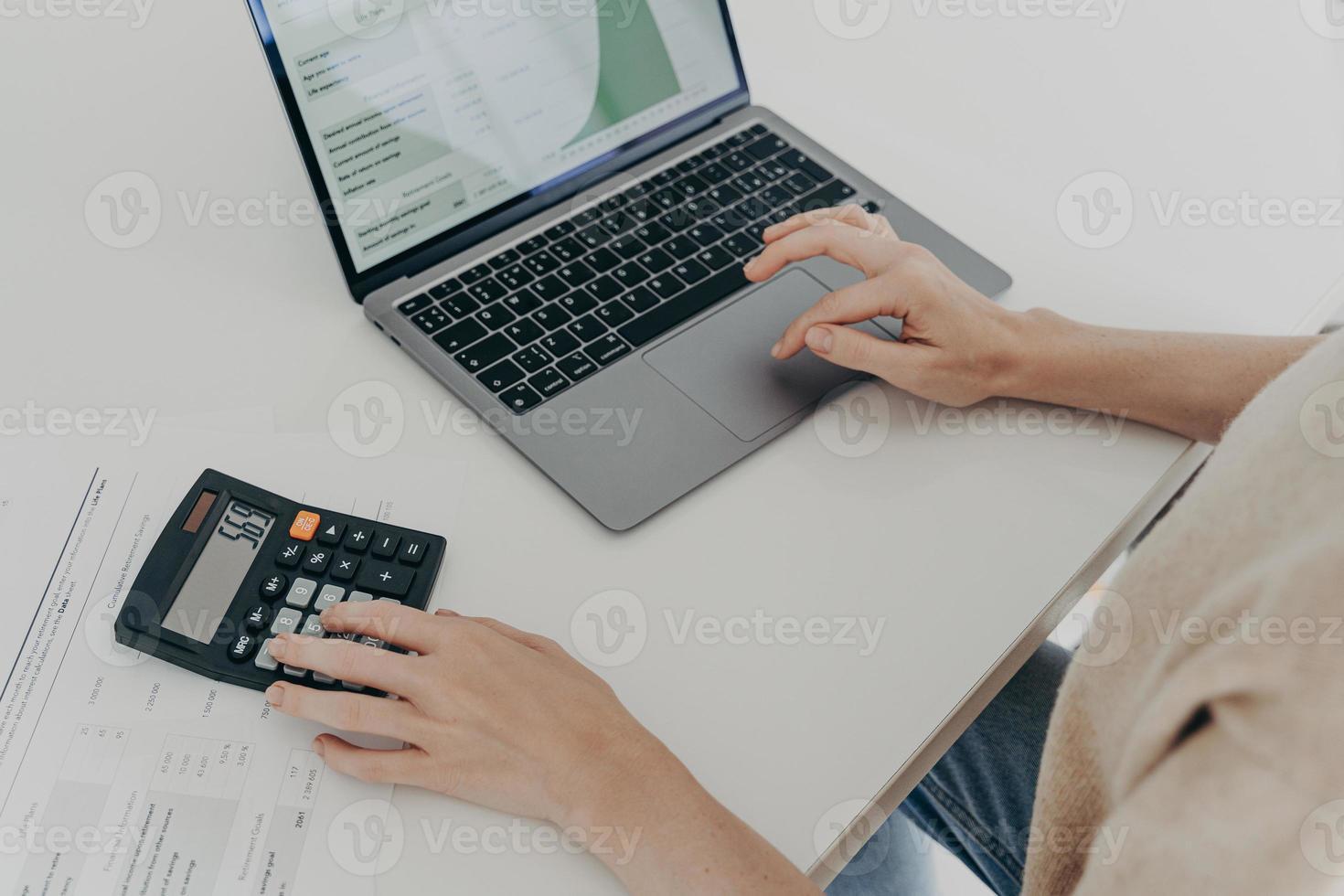 La donna irriconoscibile si siede alla scrivania con i documenti della calcolatrice del computer portatile calcola le spese mensili foto