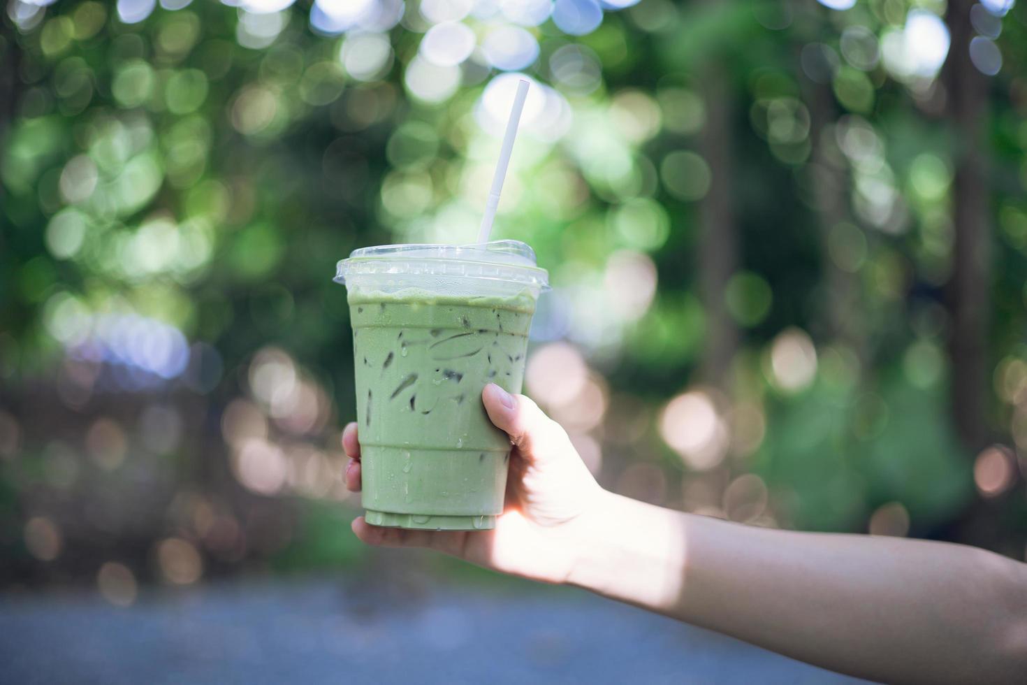 mano femminile che tiene una tazza di tè verde foto