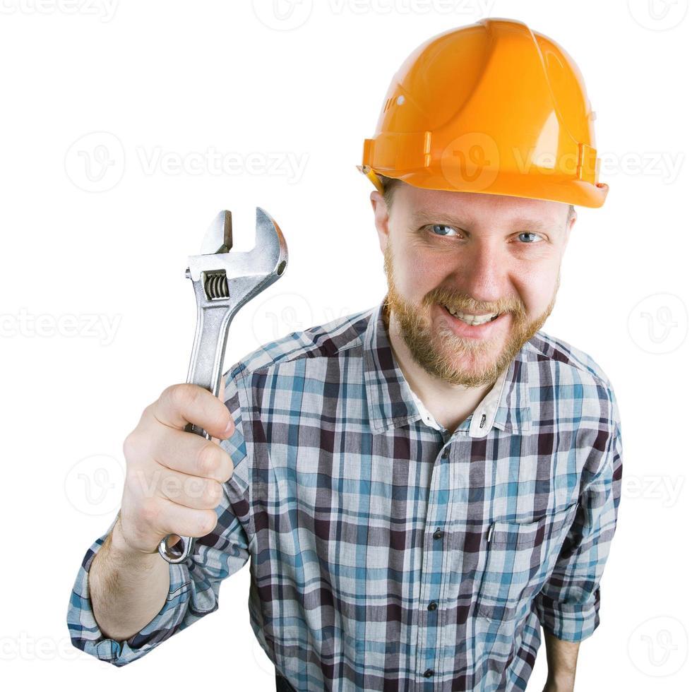 uomo con una chiave inglese in un casco foto