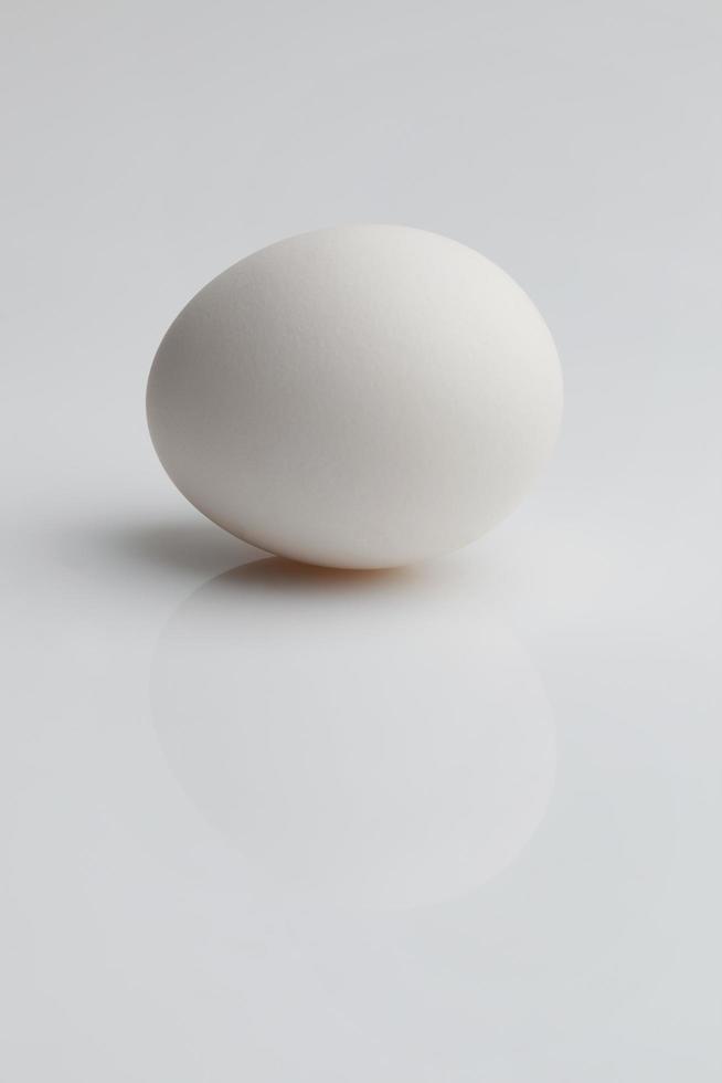l'uovo bianco giace su uno sfondo chiaro foto