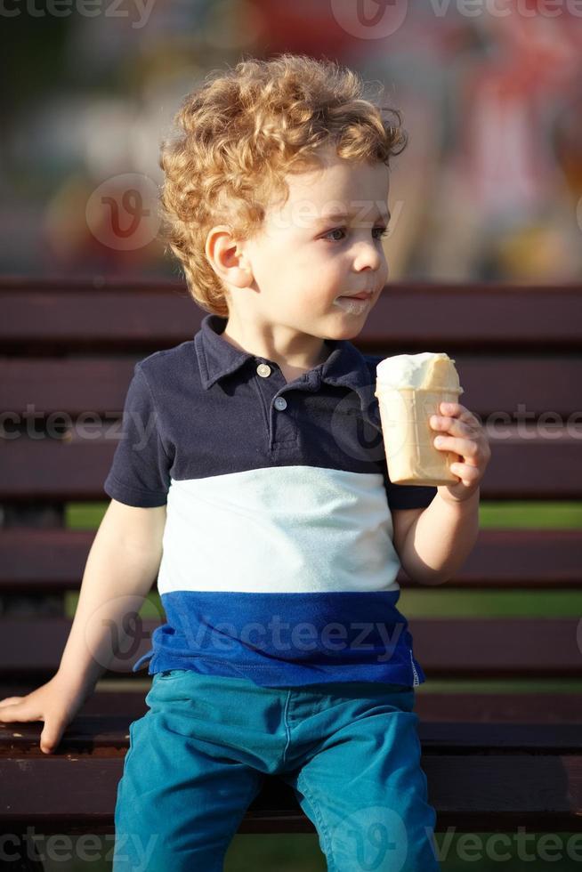 il ragazzino si siede e mangia il gelato foto
