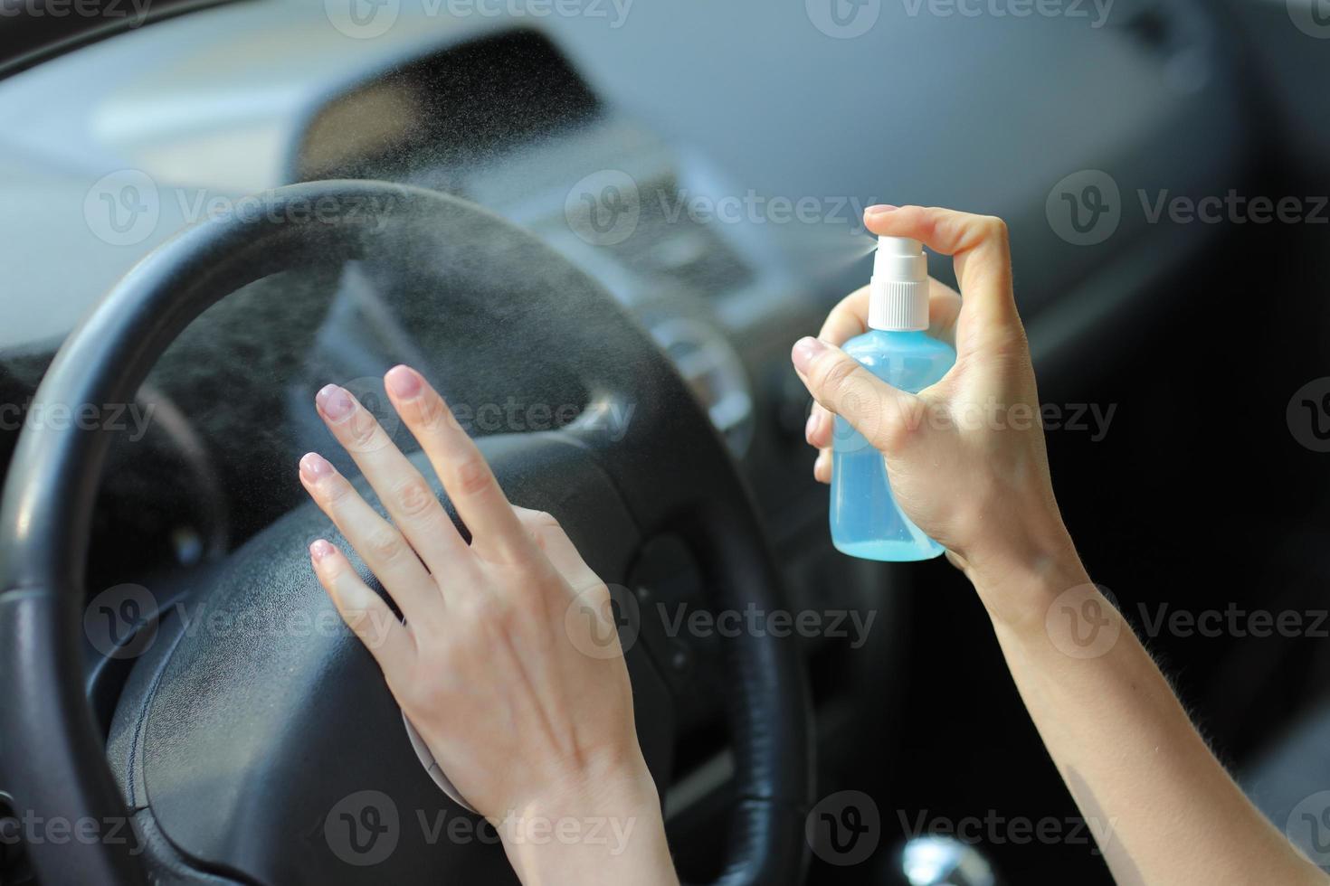 la mano della donna sta spruzzando alcol, spray disinfettante in auto, sicurezza, prevenzione dell'infezione da virus covid 19, coronavirus, contaminazione di germi o batteri. disinfettante per alcol, concetto di igiene. foto