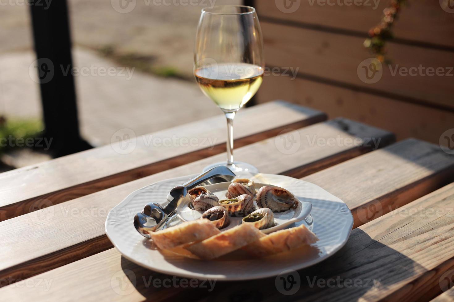 bicchiere con vino e piatto con gusci di lumaca, servito su un piatto classico bianco, con varie salse, pesto, tartufo, formaggio, pezzi di baguette francese, forchetta per conchiglia, tavolo in legno nel caffè all'aperto foto