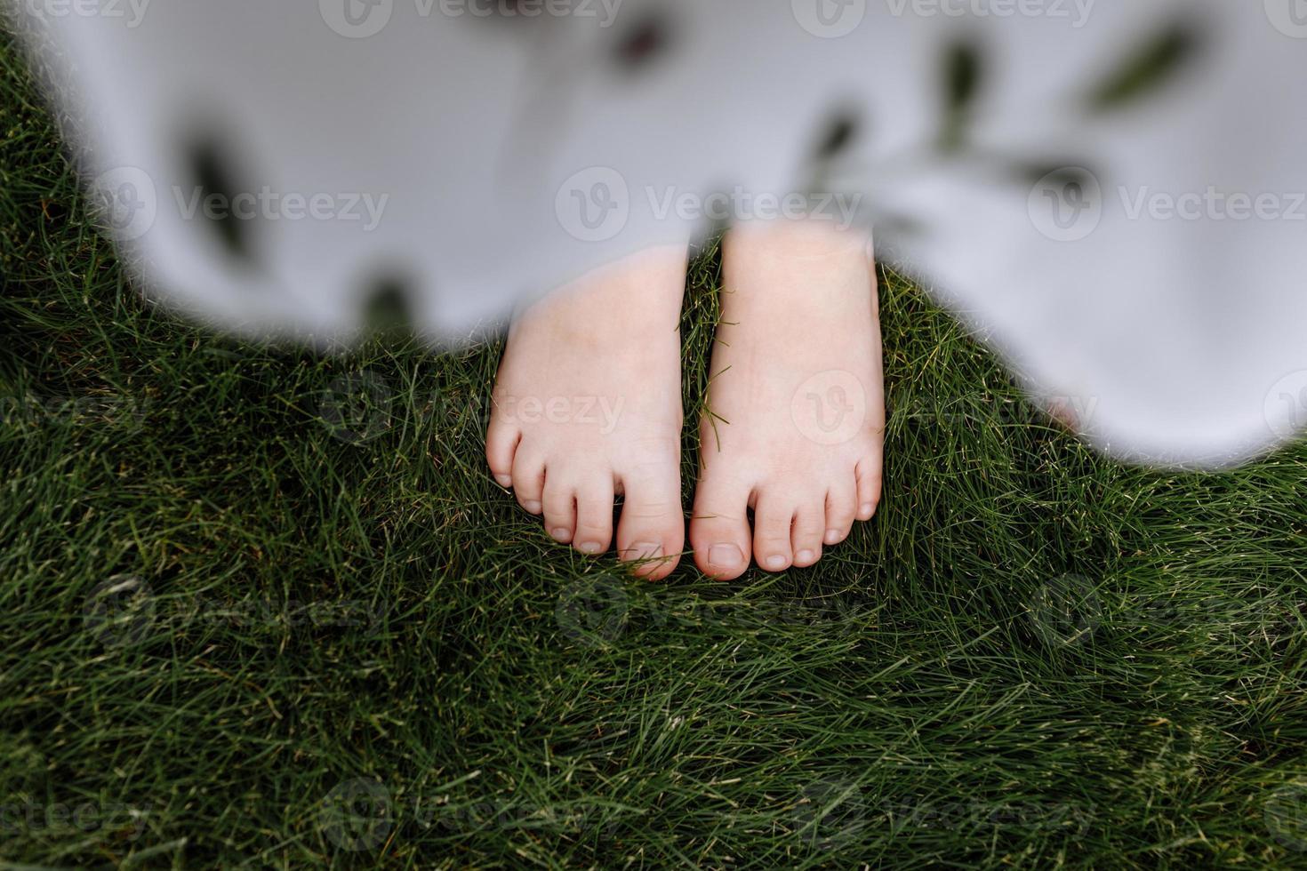 vista dall'alto primo piano dei piedi nudi del bambino sull'erba verde, concetto di natura foto