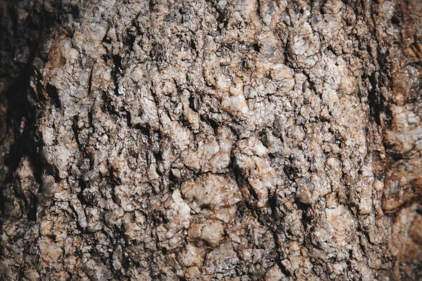 primo piano strutturato in pietra con una piccola roccia glitterata sulla superficie. foto