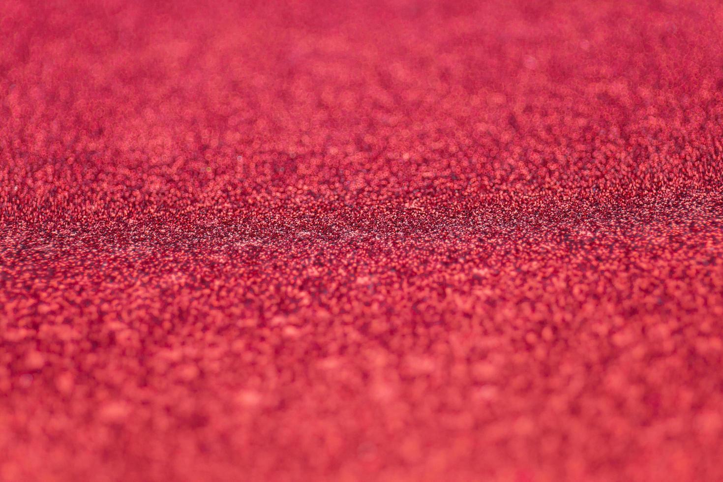 messa a fuoco selettiva su carta glitter rossa strutturata con una sottile profondità di campo foto