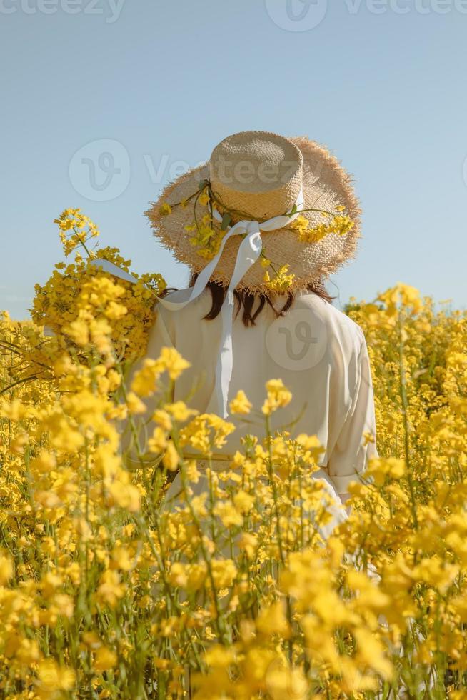 donna in piedi nel campo di colza vista posteriore da dietro foto