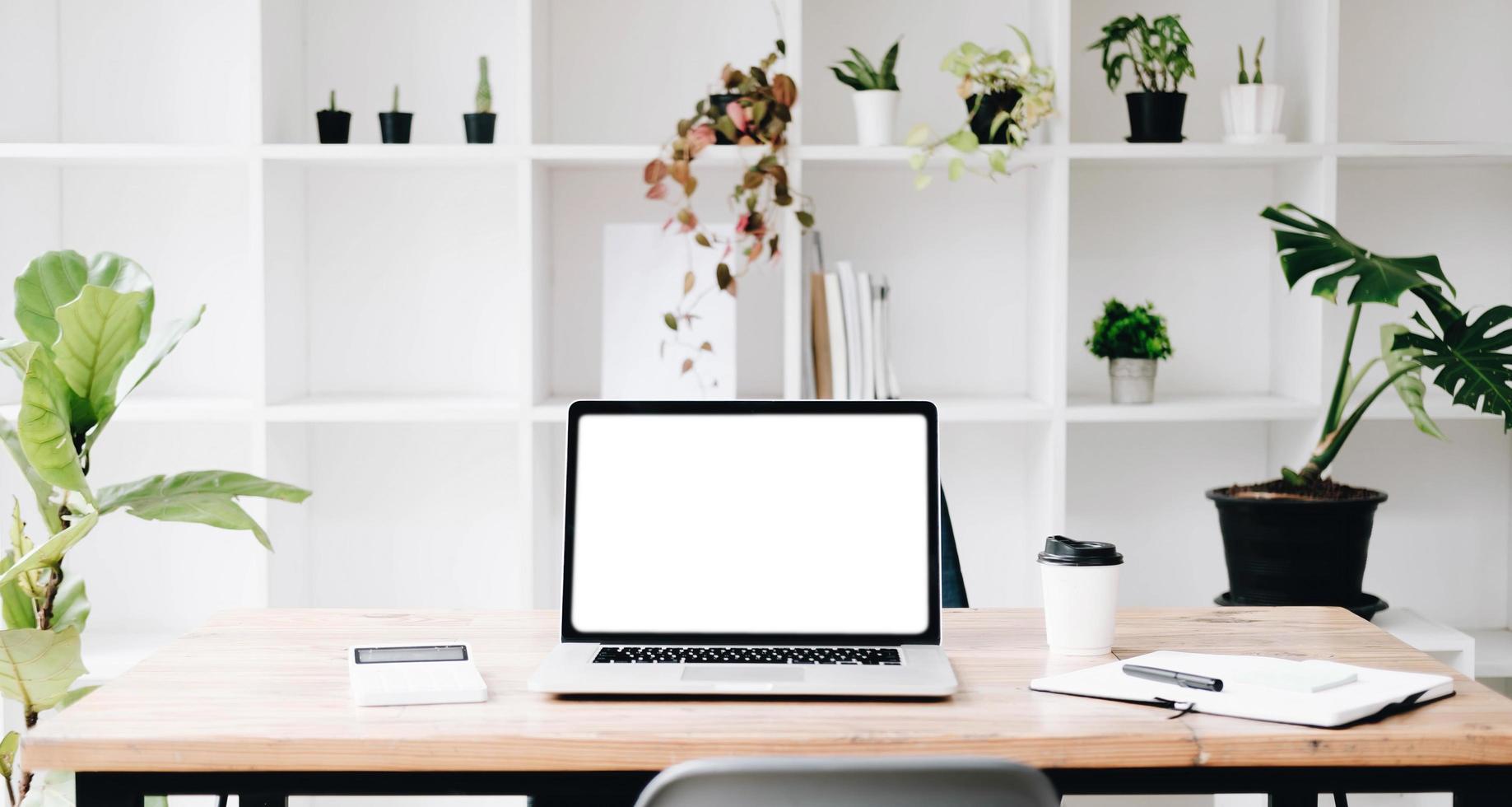 concetto di mockup sul posto di lavoro. simulare un computer desktop moderno per la casa con libri vintage, pianta d'appartamento. l'area di lavoro dell'artista con spazio di copia per i prodotti visualizza il desktop montage.mockup. foto