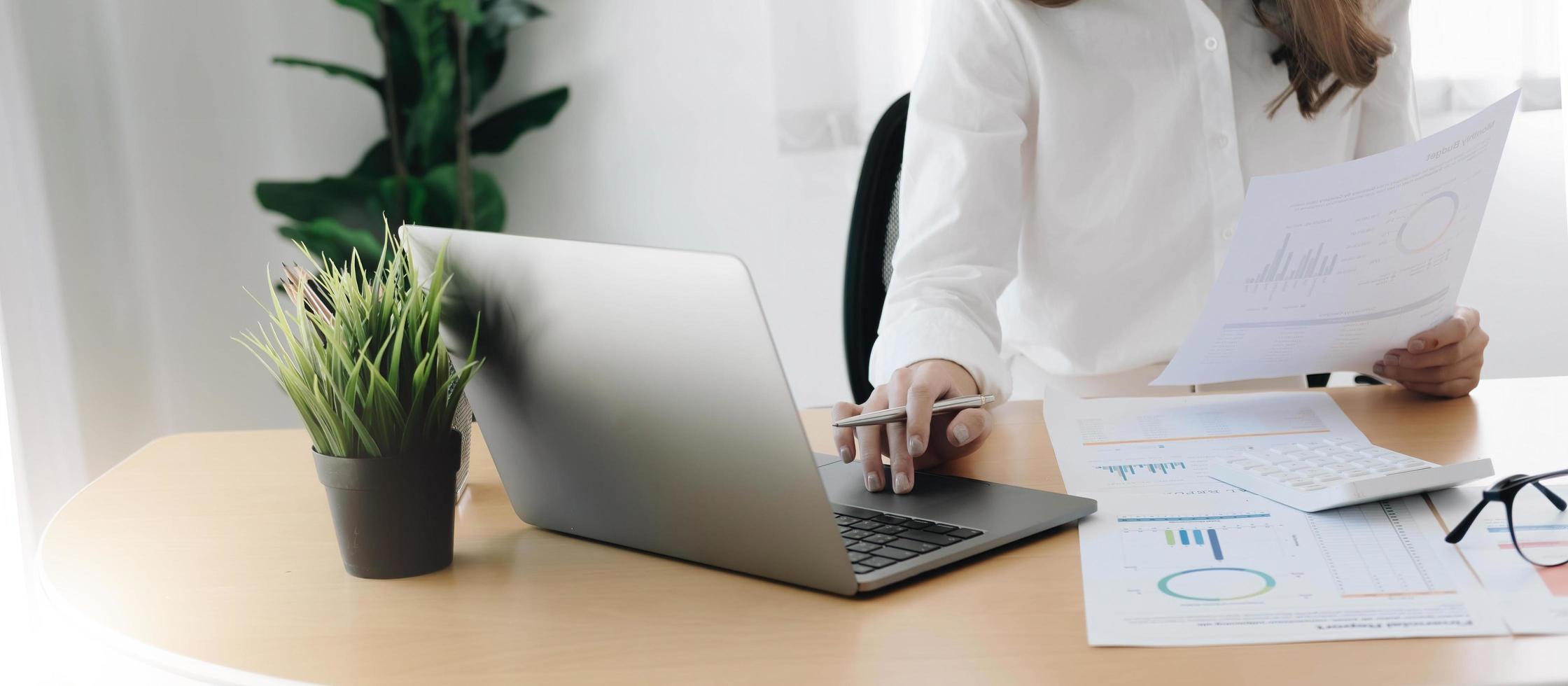 mano della donna d'affari che tiene la penna e indica la documentazione finanziaria con il diagramma della rete finanziaria. foto