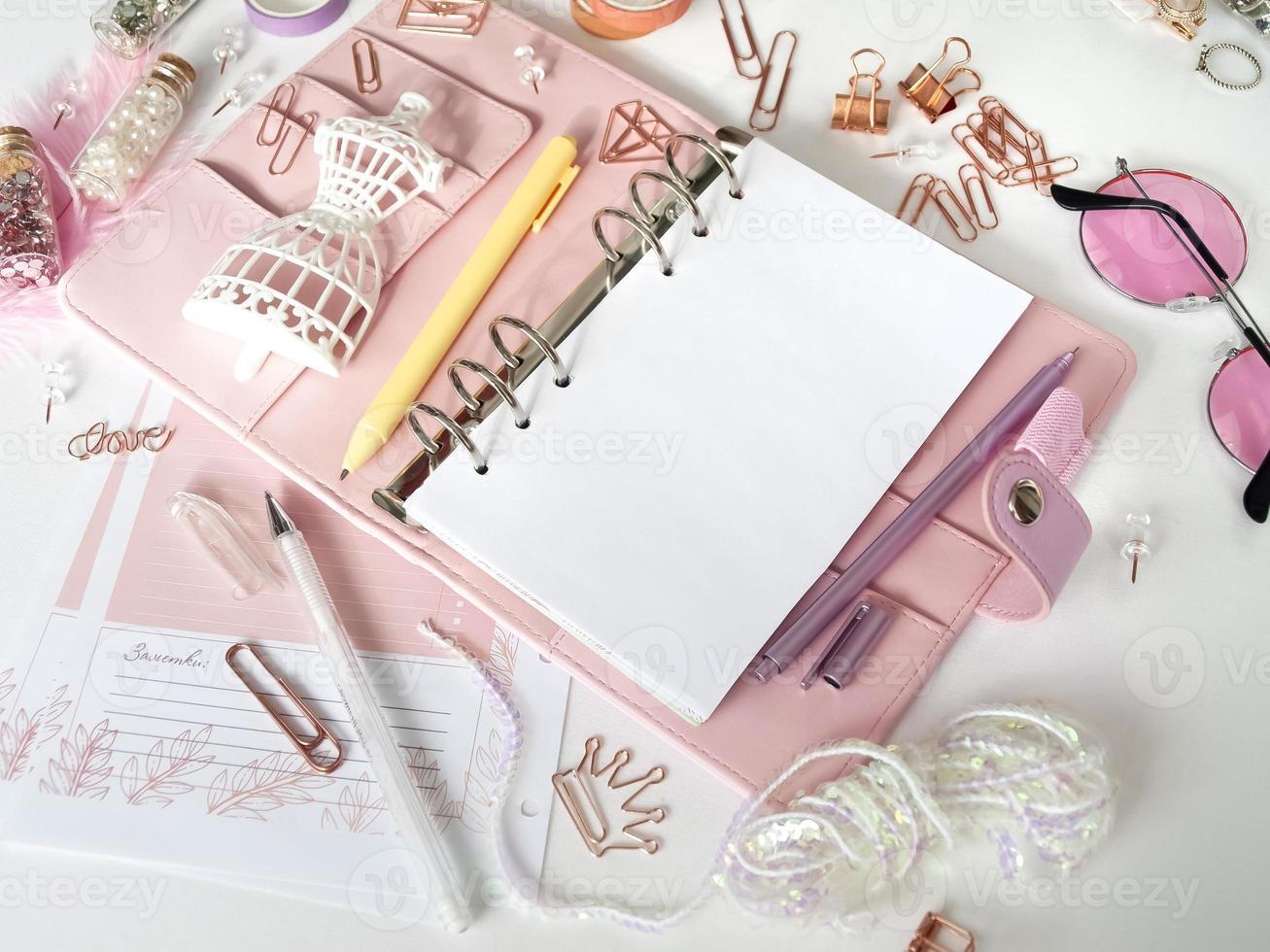 vista dall'alto di un pianificatore rosa con elementi decorativi carini. pianificatore glamour rosa con un manichino bianco. planner con pagine aperte su sfondo bianco e con bellissimi accessori penne, bottoni, spille. foto