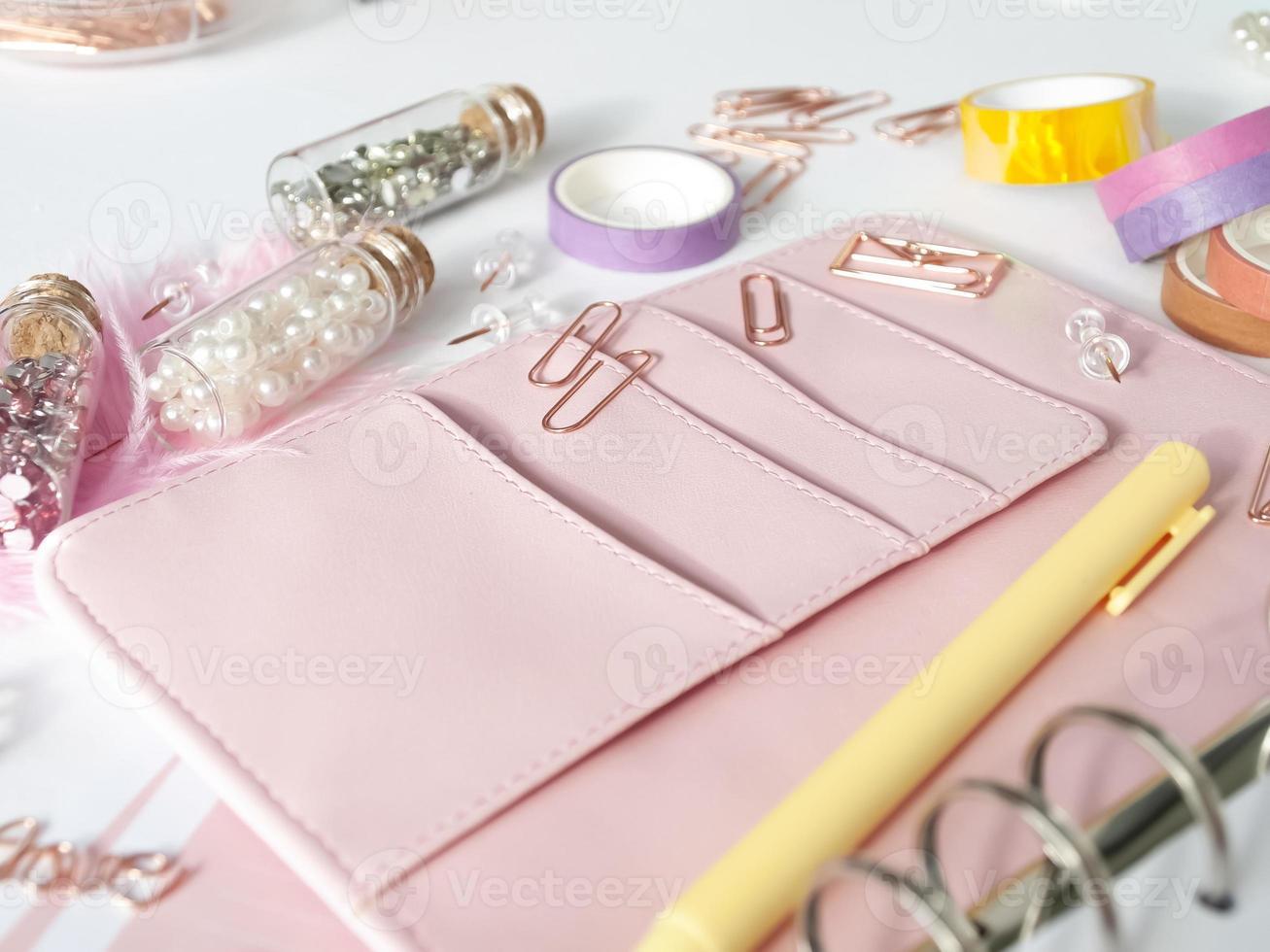 cancelleria per pianificatore in oro rosa. planner con bellissimi accessori penne, bottoni, spille e nastro colorato. penna gialla e pianificatore rosa su sfondo bianco. cristalli in bottiglie di vetro accanto al pianificatore foto