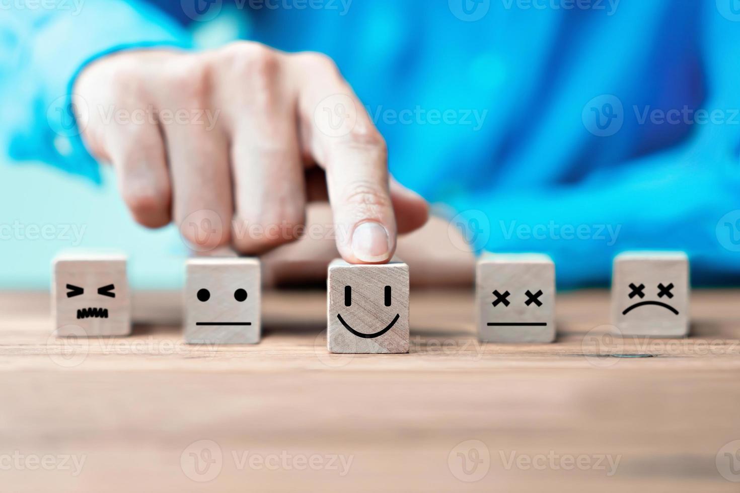 uomo d'affari sceglie una faccia felice icone emoticon. servizio, concetto di comunicazione foto