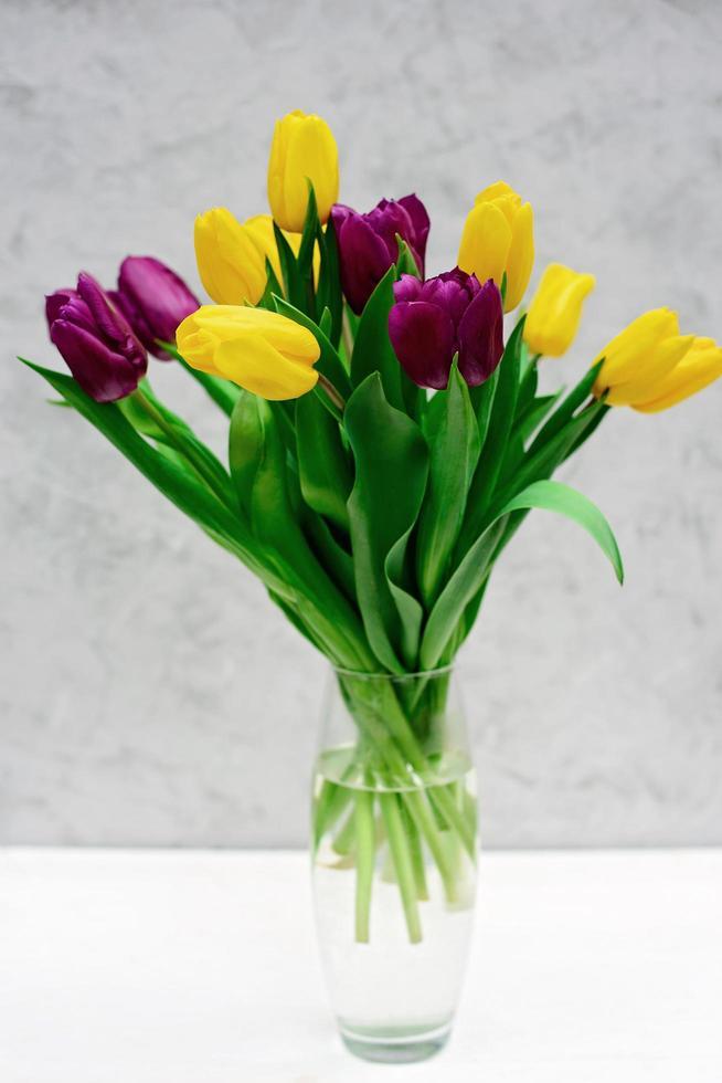 bouquet di fiori di tulipano primaverile viola e giallo in un vaso di vetro su uno sfondo chiaro. festa della mamma. giornata internazionale della donna. foto
