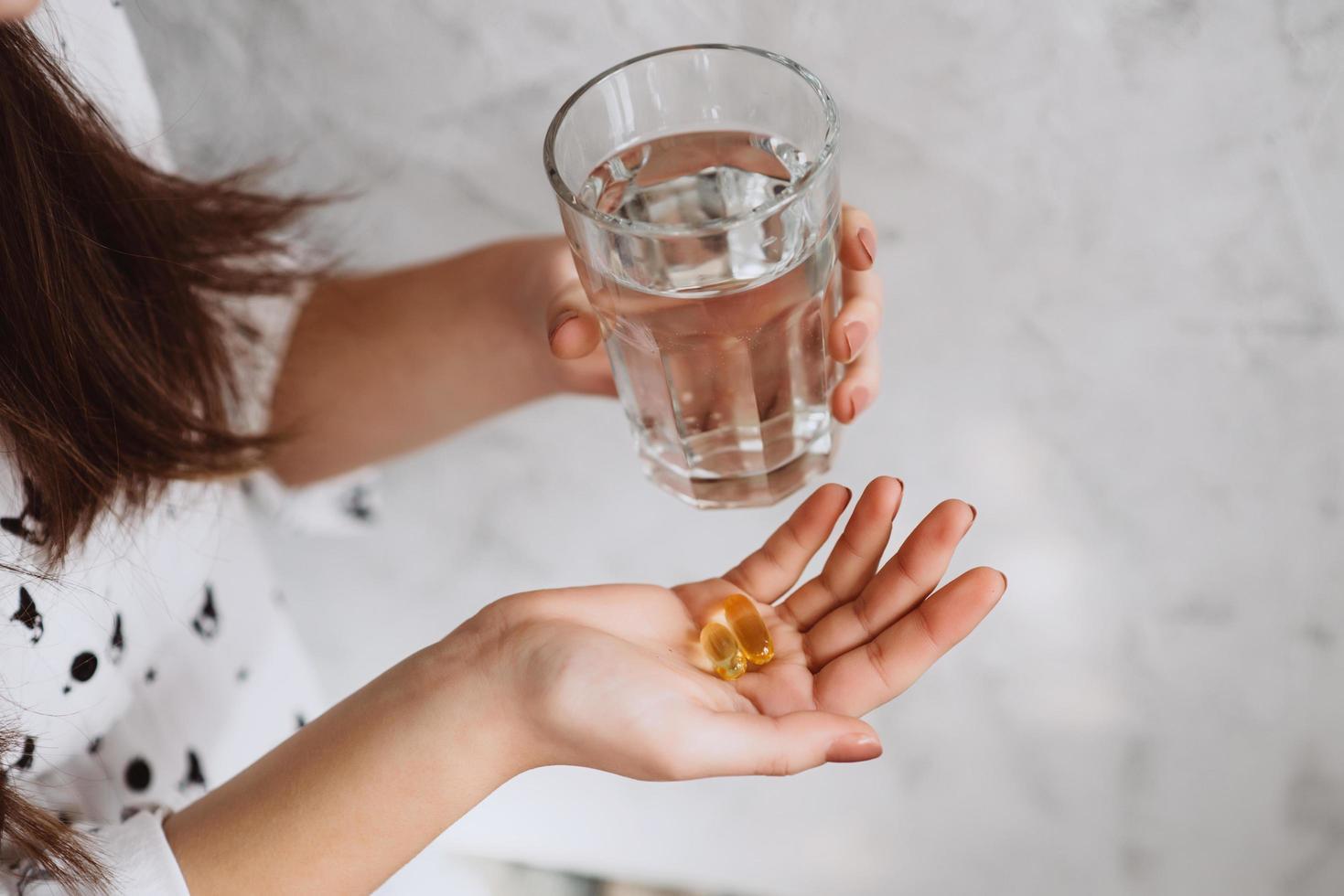mani della ragazza con pillole con olio di fegato di merluzzo omega-3 e un bicchiere di acqua fresca. foto