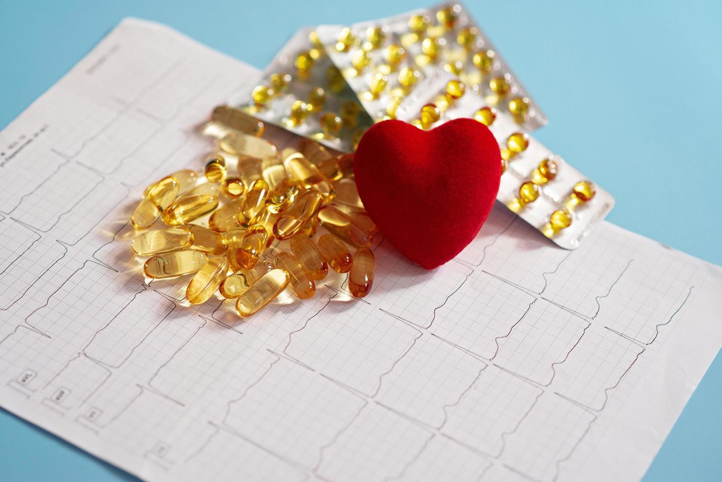 le capsule di omega-3 si trovano su un cardiogramma accanto a un cuore rosso. olio di pesce in compresse. supporto sanitario e trattamento del cuore. foto
