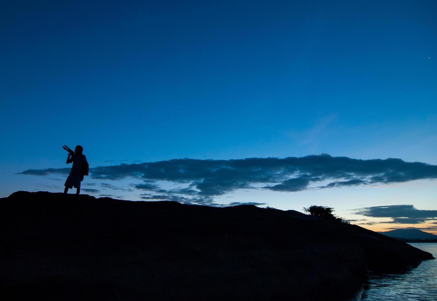 sagoma del fotografo che fotografa il paesaggio durante l'alba foto
