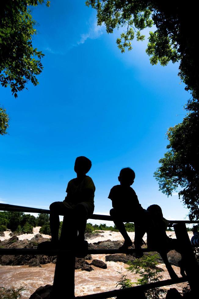 ragazzino seduto su una recinzione a khone phapheng water fall o fiume mekong a champasak, nel sud del laos, una delle cascate più grandi e belle in asia e nel mondo foto