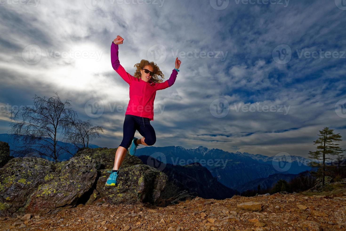 ragazza salta dalle rocce in montagna durante un allenamento foto
