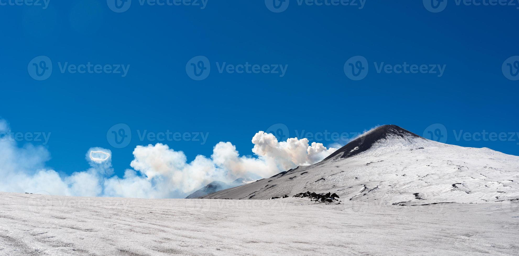 cratere sommitale del vulcano Etna con fumo ad anello spettacolare fenomeno di areola di vapore durante l'eruzione foto