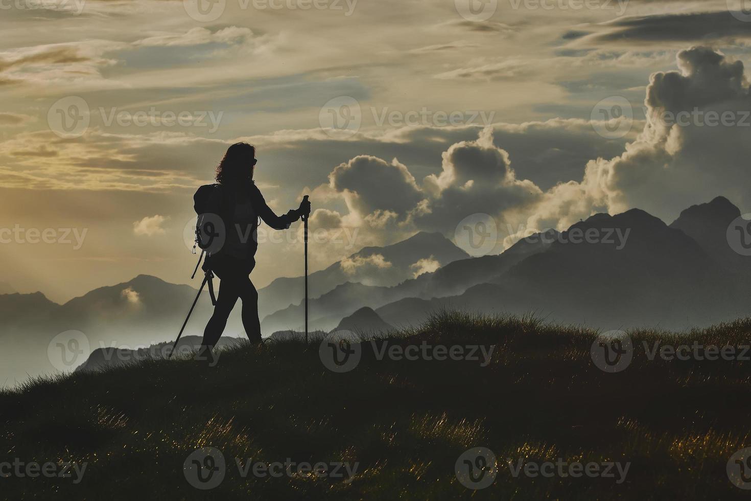 camminare in solitudine sulle alpi. una donna con lo sfondo di montagne astratte tra le nuvole foto