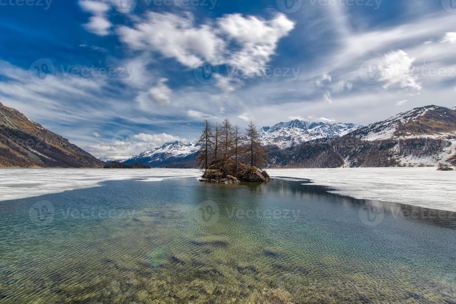 disgelo nel lago delle alpi svizzere. piccolo isolotto foto