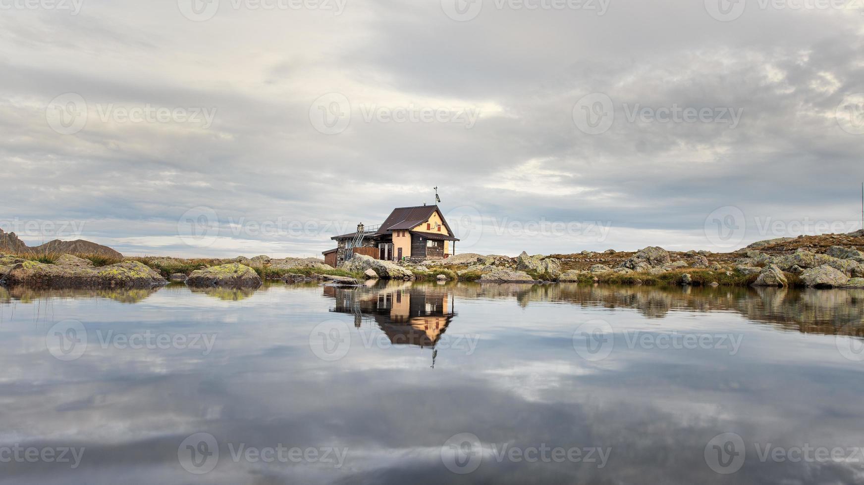 piccolo rifugio alpino specchiato nel lago di montagna foto