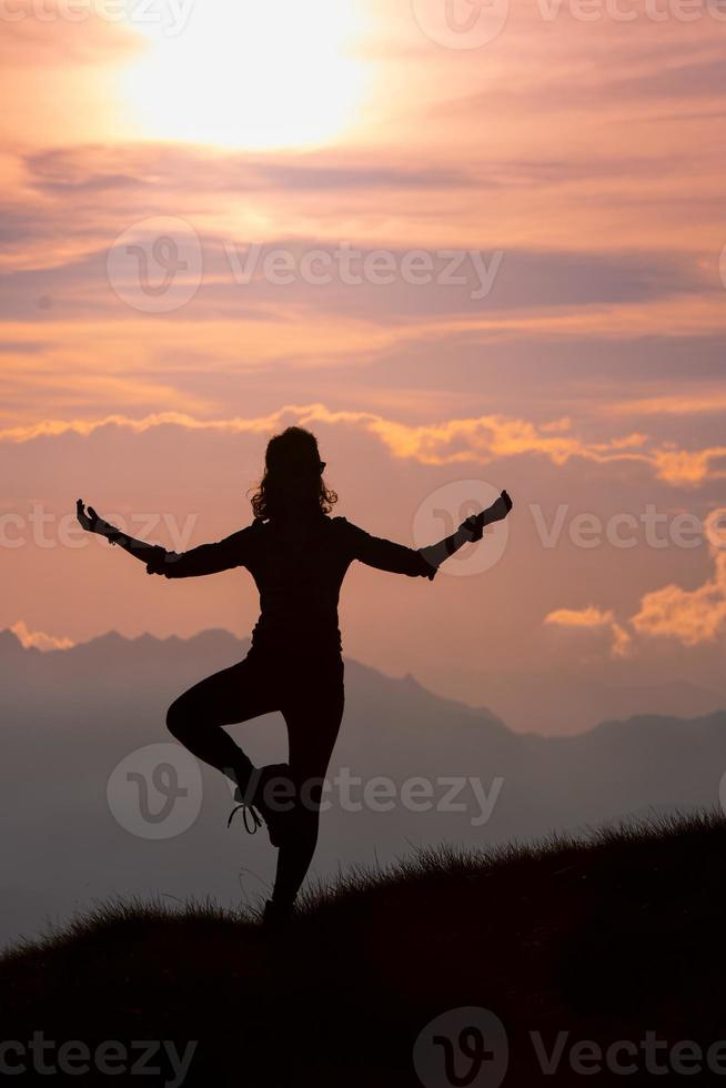ragazza pratica posizioni yoga in montagna durante un'escursione foto
