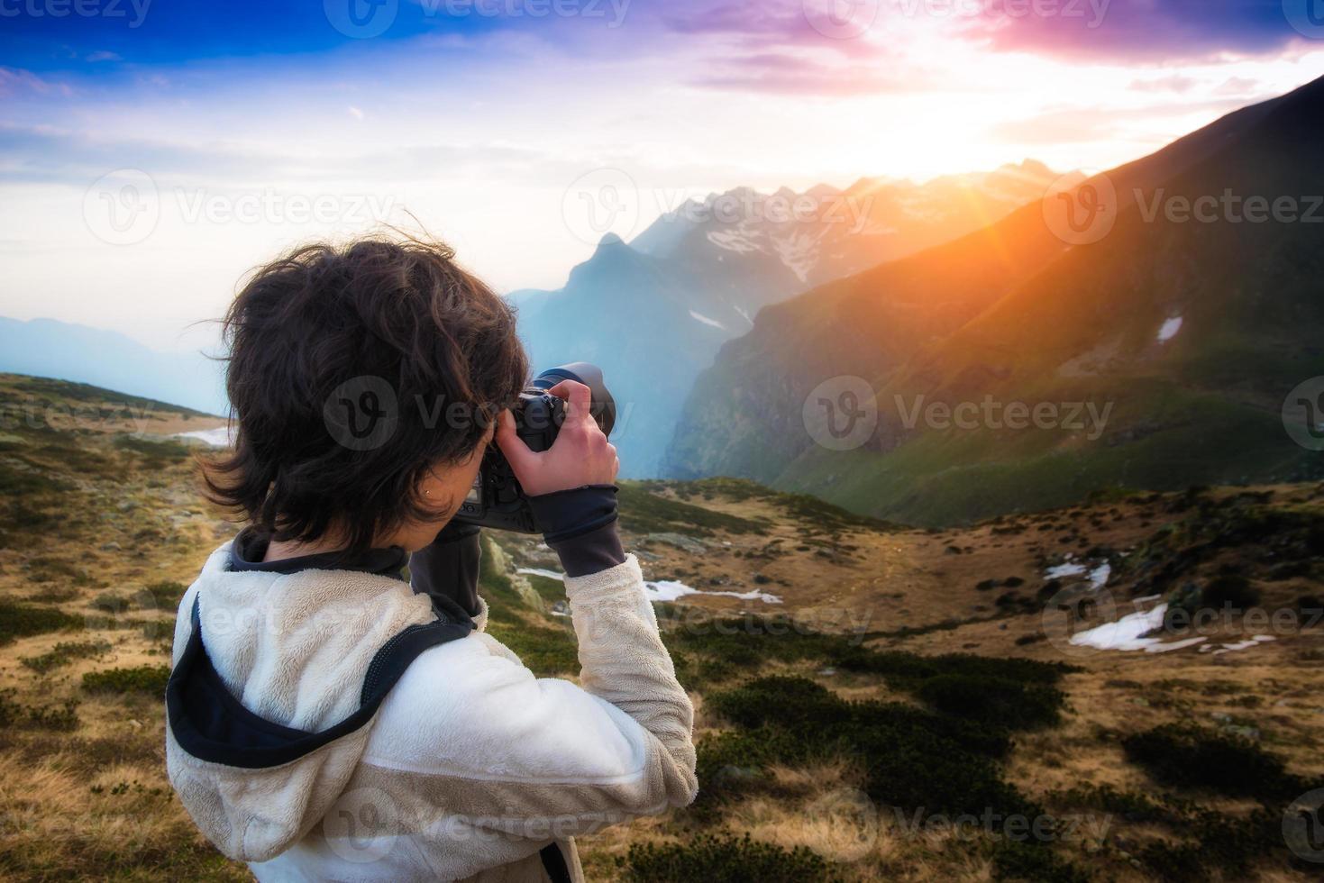 ragazza che fotografa il tramonto in montagna foto