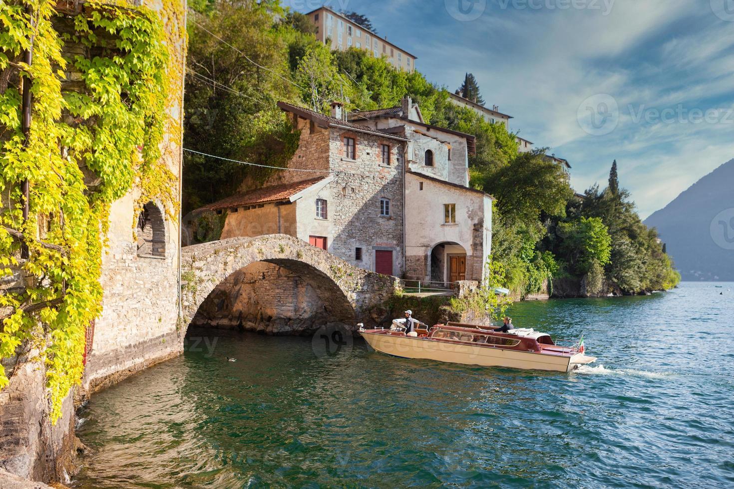 stile turistico motoscafo in legno che si avvicina a un vecchio ponte di pietra sul lago di como foto