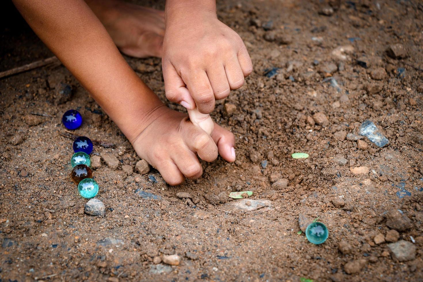 bambino che gioca a palline di vetro per terra foto