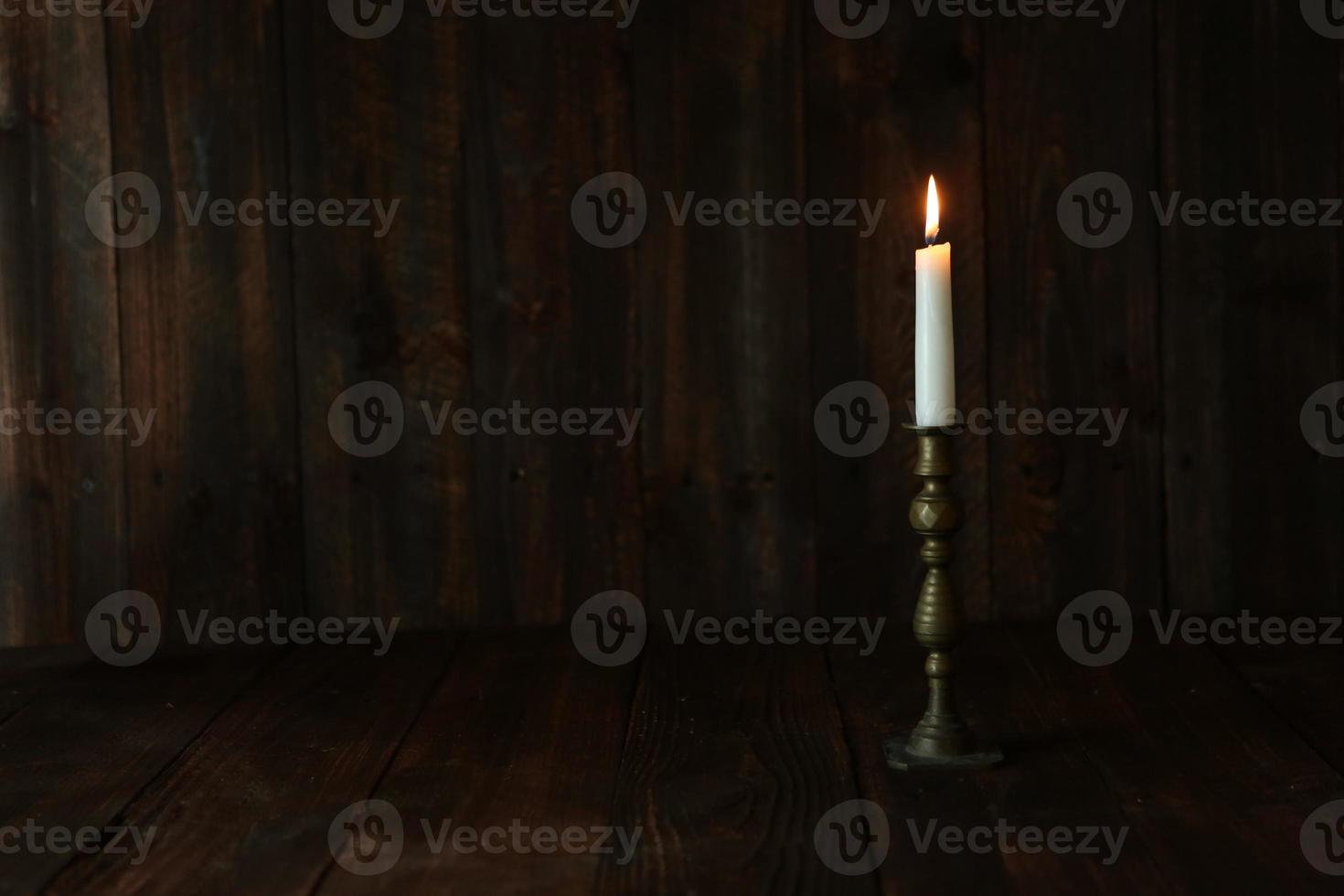 candela accesa su un vecchio fondo rustico in legno foto