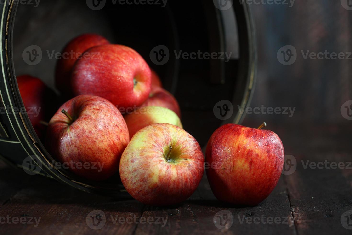 barile casalingo pieno di mele rosse su sfondo di legno grunge foto