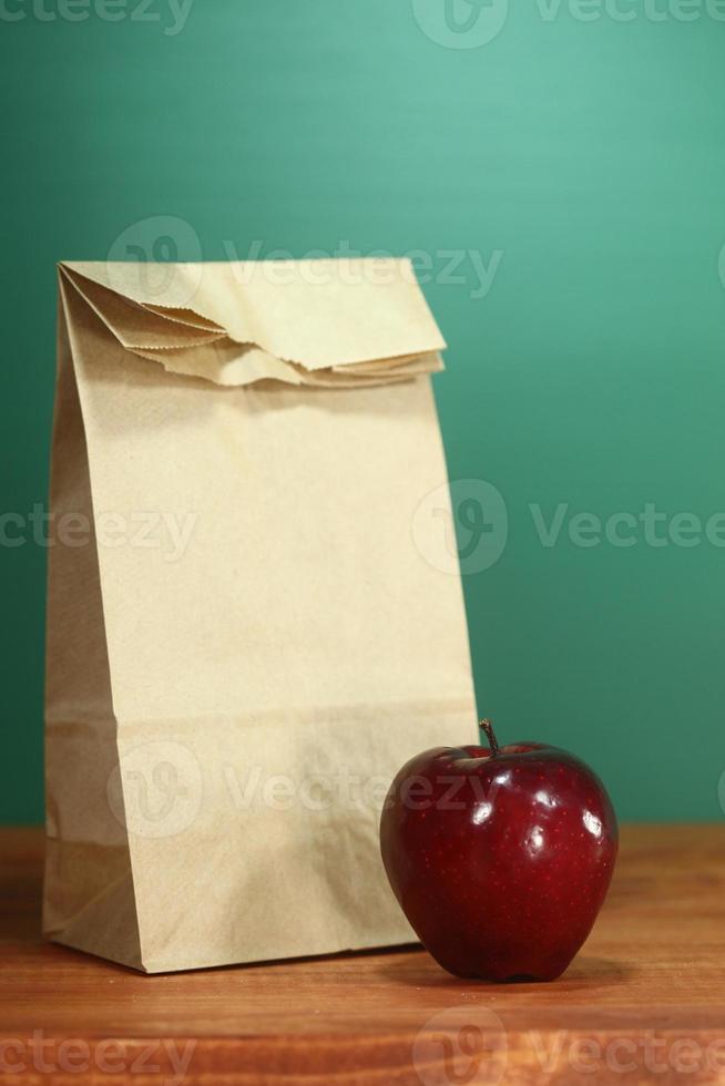 sacco pranzo a scuola seduto sulla scrivania dell'insegnante foto