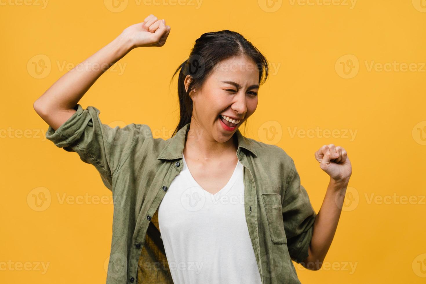 giovane donna asiatica con espressione positiva, gioiosa ed eccitante, vestita di stoffa casual su sfondo giallo con spazio vuoto. felice adorabile donna felice esulta successo. concetto di espressione facciale. foto