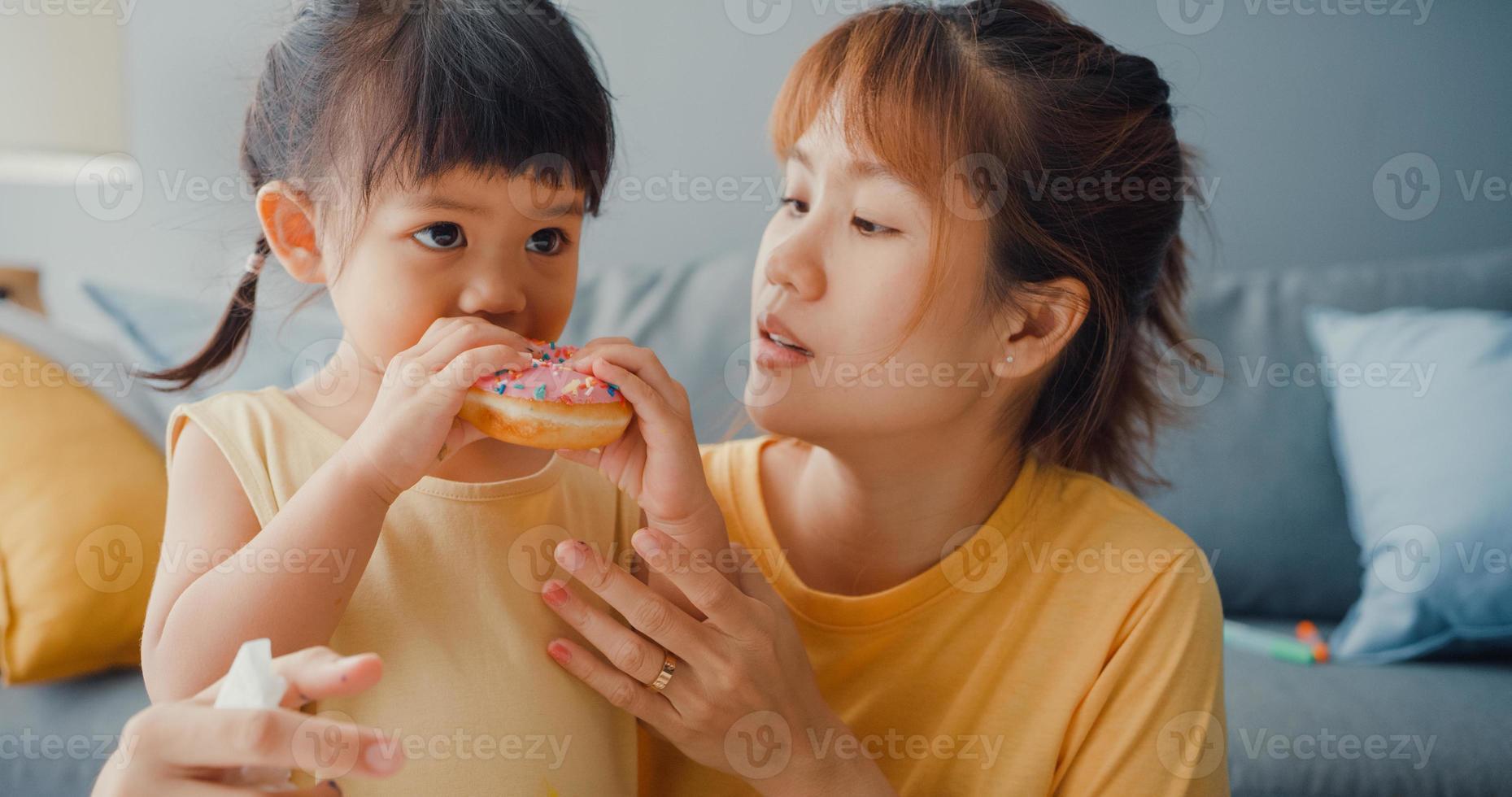 felice allegra famiglia asia mamma e bambina che mangiano ciambelle e si divertono rilassati goditi sul divano nel soggiorno di casa. passare del tempo insieme, distanza sociale, quarantena per il coronavirus. foto