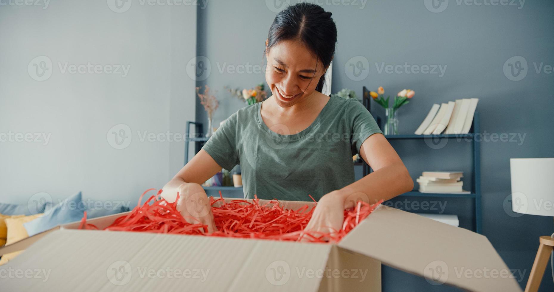 felice bella signora asiatica unboxing cartone consegna pacchetto dal mercato online nel soggiorno di casa. acquirente soddisfatto in unboxing di merci su Internet, shopping online e concetto di consegna. foto