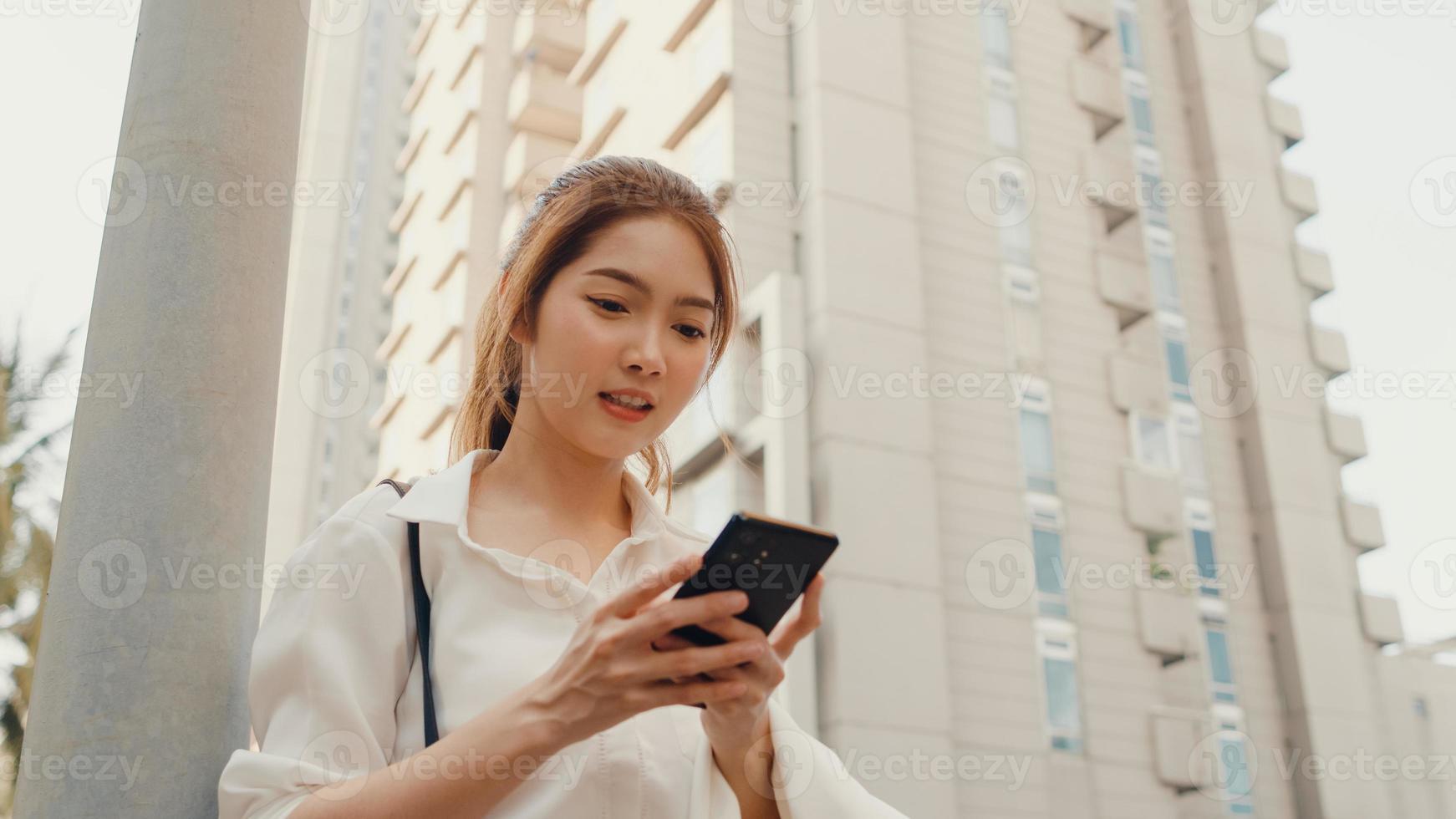 giovane imprenditrice asiatica di successo in abiti da ufficio di moda utilizzando lo smartphone e digitando un messaggio di testo mentre si cammina da soli all'aperto nella città moderna urbana al mattino. concetto di affari in movimento. foto