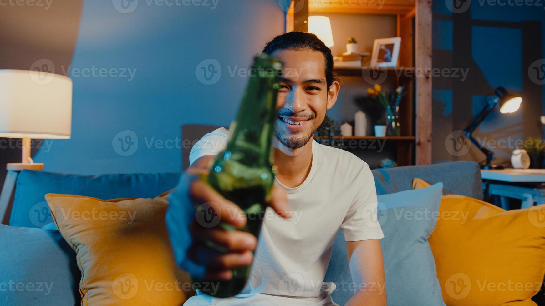 felice giovane uomo asiatico che guarda la macchina fotografica godetevi l'evento della festa notturna online con gli amici brindare bevendo birra tramite videochiamata online nel soggiorno di casa, stare a casa in quarantena, concetto di distanza sociale. foto